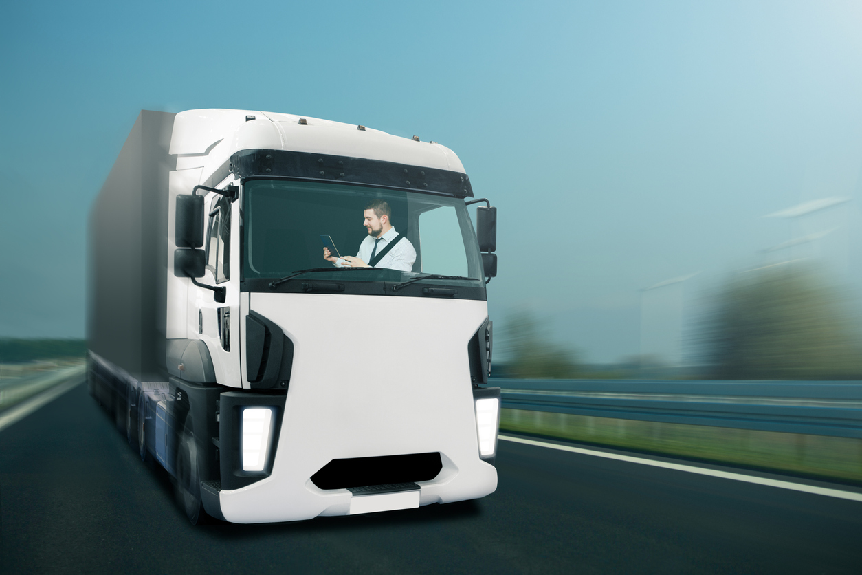 Driver looks into the digital tablet while the self driving truck is driving